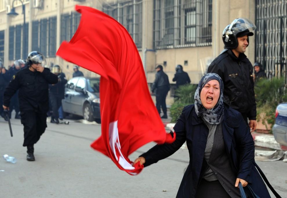 10. TUNEZJA, Tunis, 14 stycznia 2011: Kobieta z flagą Tunezji podczas zamieszek na ulicy w stolicy Tunezji. AFP PHOTO / FETHI BELAID