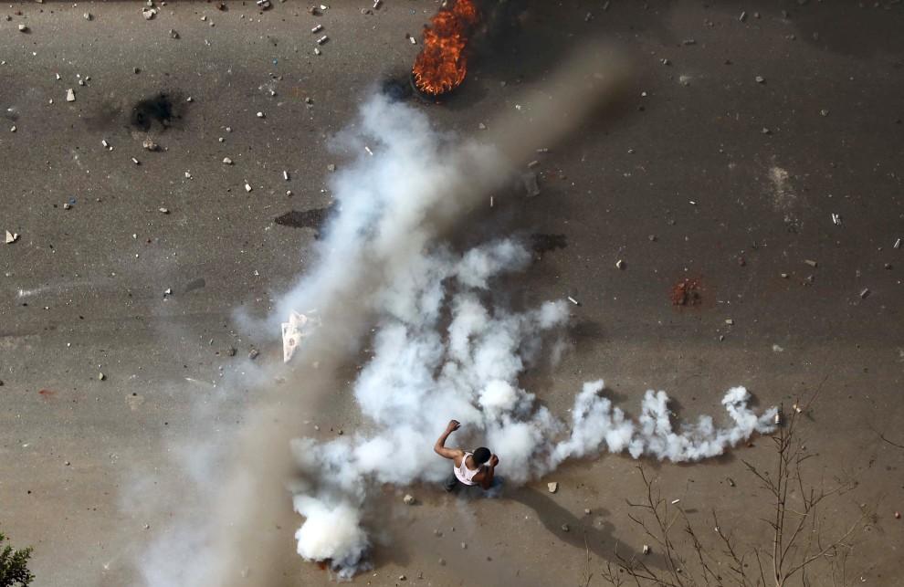 11. EGIPT, Kair, 28 stycznia 2011: Mężczyzna stara się wykopać pojemnik z gazem łzawiącym wystrzelony przez policjantów. AFP PHOTO/KHALED DESOUKI