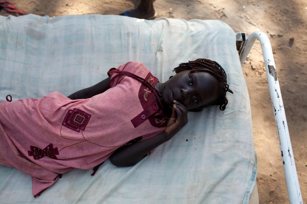 12. SUDAN, Dżuba, 5 stycznia 2011: Dziewczynka leży na łóżku, które w raz z pozostałym dobytkiem przywieźli jej rodzice. AFP PHOTO/ Yasuyoshi Chiba