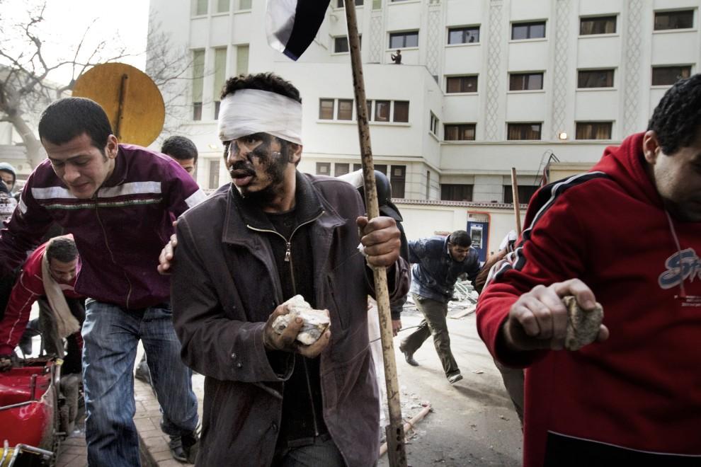 12. EGIPT, Kair, 29 stycznia 2011: Protestujący chronią się przed ostrzałem policji. AFP PHOTO/MARCO LONGARI