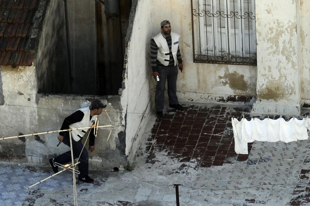 12. TUNEZJA, Tunis, 16 stycznia 2011: Policjanci na dachu jednego z domów w centrum miasta. AFP PHOTO / FRED DUFOUR