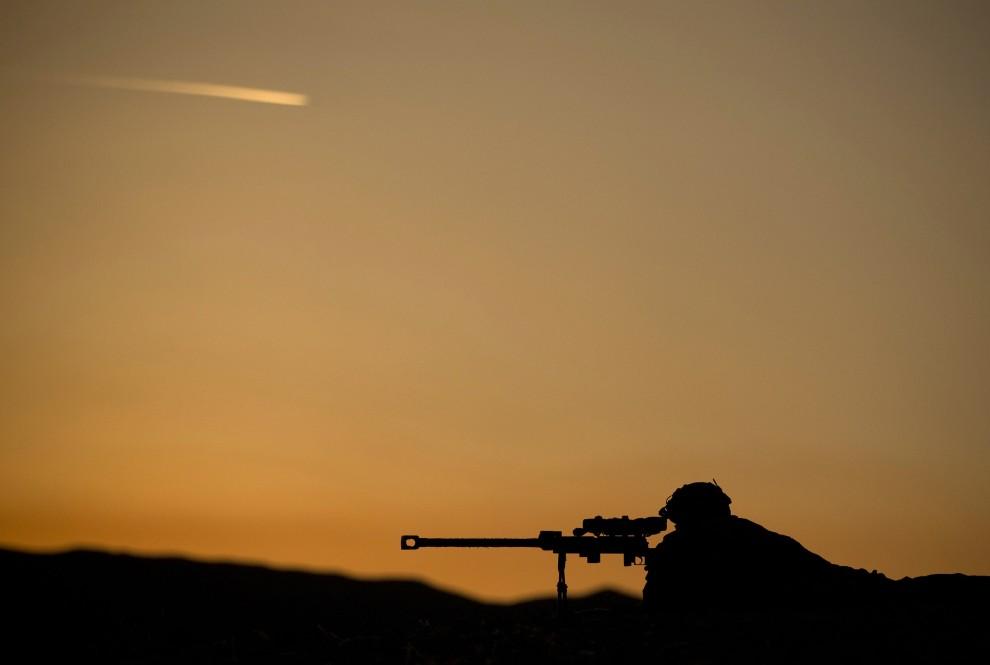 13. AFGHANISTAN, Tora Bora, 21 stycznia 2011: Francuski żołnierz obserwuje okolicę przez lunetę zamontowaną na karabinie snajperskim. AFP PHOTO/JOEL SAGET