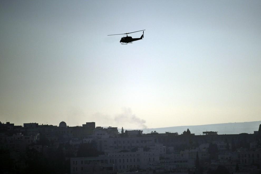 13. TUNEZJA, Tunis, 16 stycznia 2011: Wojskowy śmigłowiec patroluje przestrzeń nad miastem w trakcie zamieszek. AFP PHOTO / FRED DUFOUR