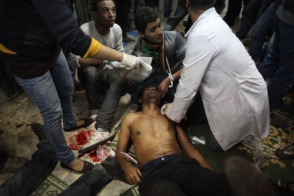13. EGIPT, Kair, 29 stycznia 2011: Ekipa medyczna, która pracuje w jednym z meczetów, udziela pomocy mężczyźnie rannemu podczas zamieszek. (Foto: Peter Macdiarmid/Getty Images)