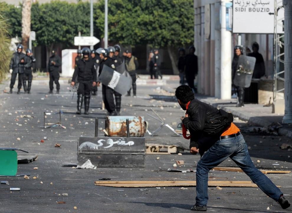 14. TUNEZJA, Regueb, 10 stycznia 2011: Mężczyzna obrzuca kamieniami policjantów. AFP PHOTO/STR