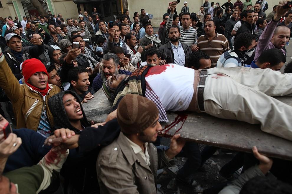 14. EGIPT, Kair, 29 stycznia 2011: Protestujący niosą rannego mężczyznę. (Foto: Peter Macdiarmid/Getty Images)