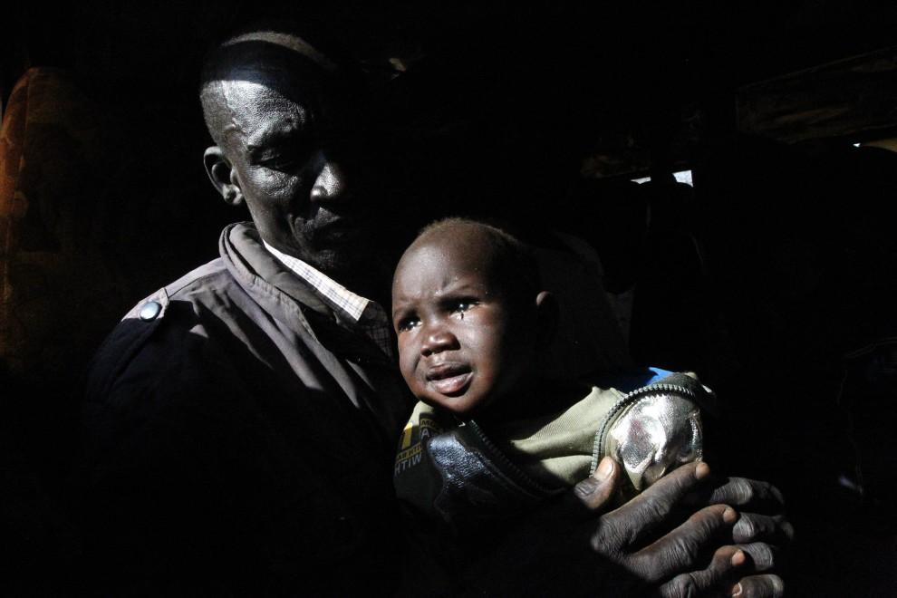 15. SUDAN, Chartum, 6 stycznia 2011: Ojciec z dzieckiem na rękach w autobusie zmierzającym na południe kraju. AFP PHOTO/KHALED DESOUK
