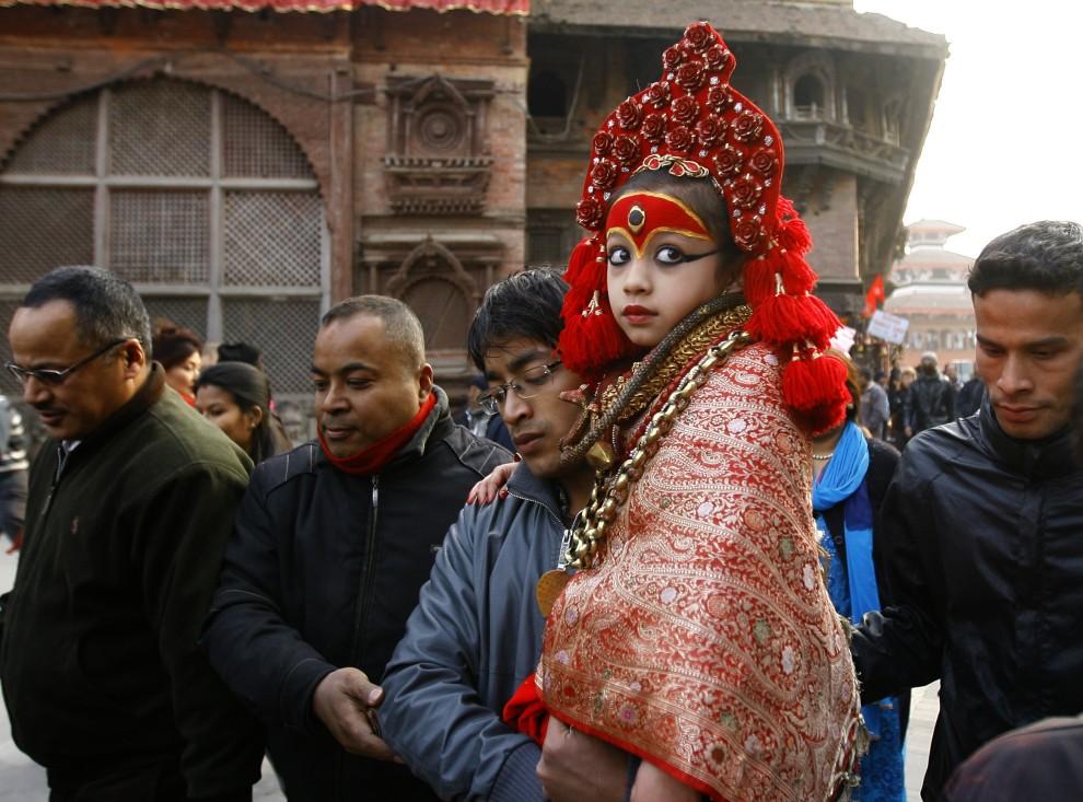 16. NEPAL, Kathmandu, 19 stycznia 2011: Kapłan niesie na rękach nepalską żyjącą boginię Kumari. AFP PHOTO/Prakash MATHEMA