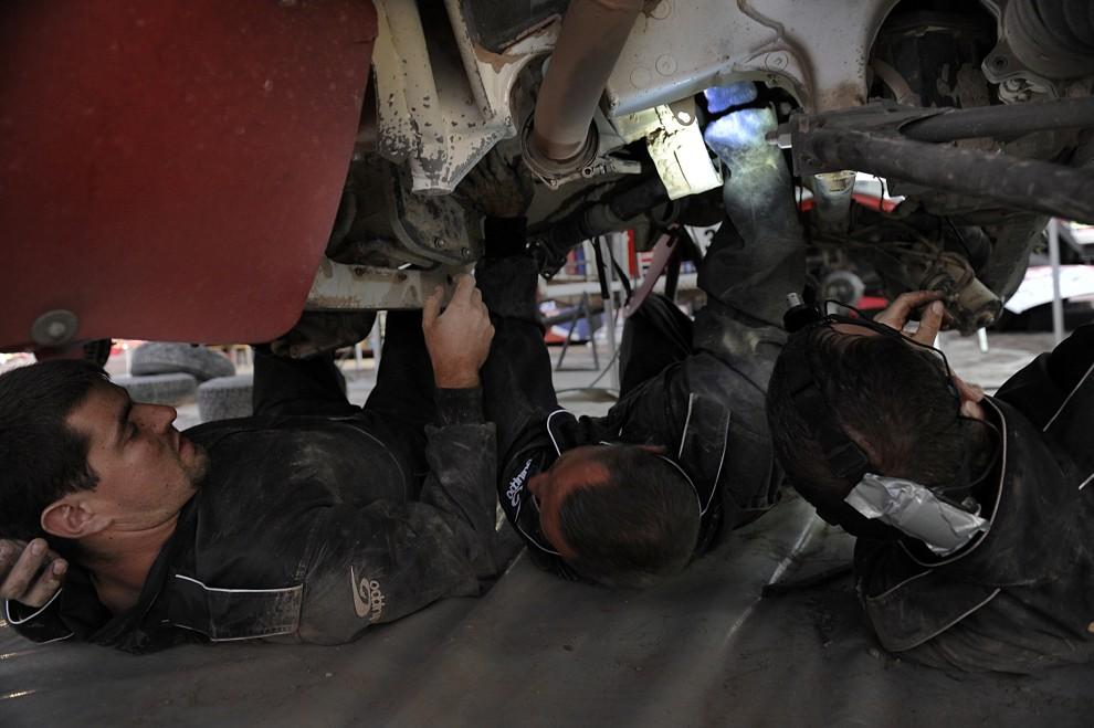 16. CHILE, Iquique, 6 stycznia 2011: Mechanicy usuwają usterki po zakończeniu piątego  etapu z Calama do Iquique. AFP PHOTO / Daniel GARCIA