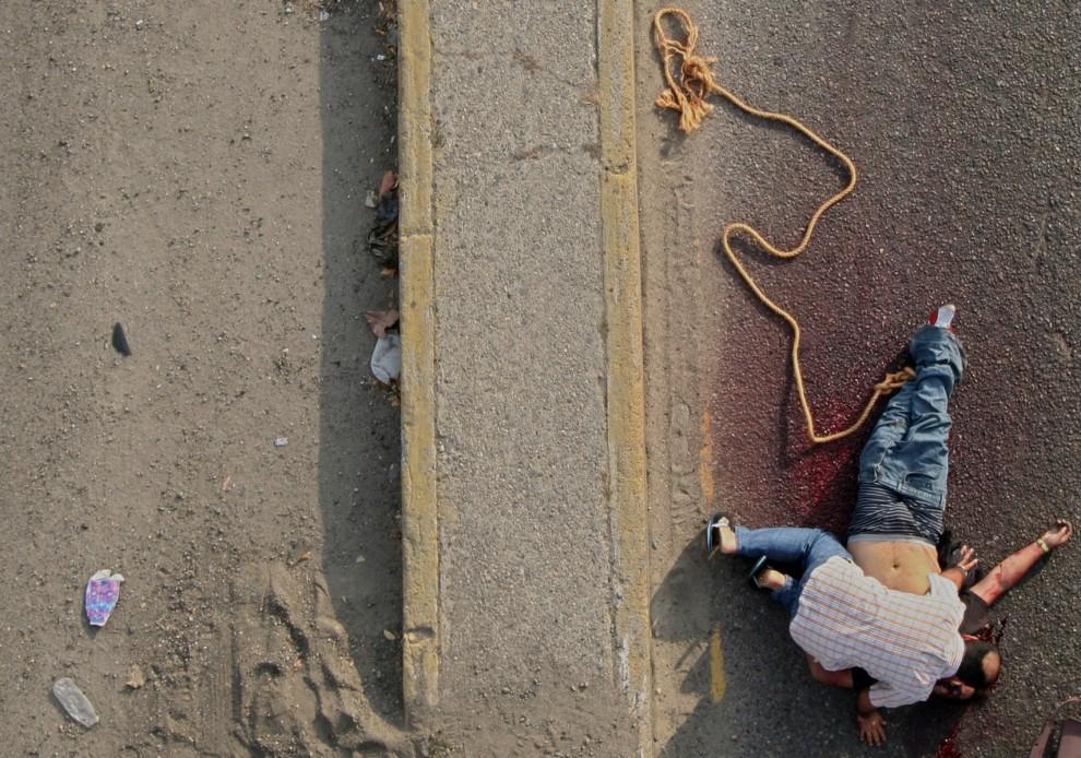 16. MEKSYK, Acapulco, 9 stycznia 2011: Mężczyzna rozpacza nad ciałem bliskiej osoby – ofiary wojny pomiędzy handlarzami narkotyków. AFP PHOTO/Pedro Pard
