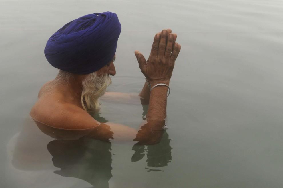 17. INDIE, Amritsar, 1 stycznia 2011: Sikh podczas kąpieli w świętych wodach wewnątrz Złotej Świątyni. AFP PHOTO/NARINDER NANU