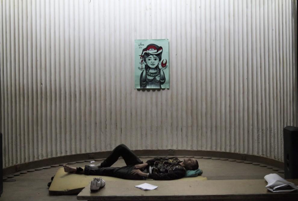 17. EGIPT, Kair, 28 stycznia 2011: Ranny mężczyzna leży na podłodze w siedzibie największej partii opozycyjnej. AFP PHOTO/MARCO LONGARI