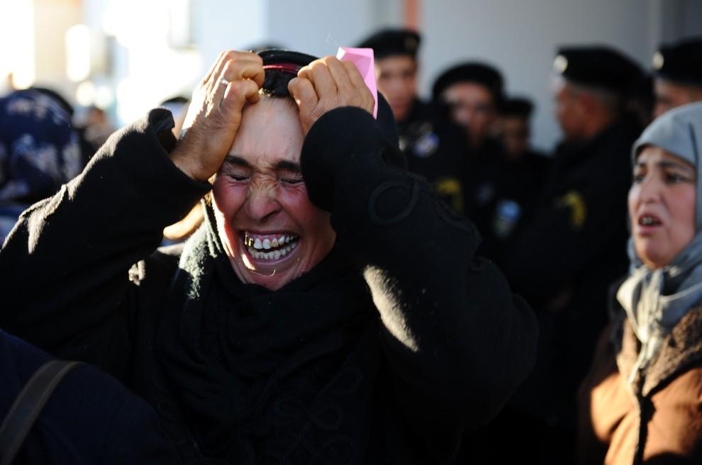 """17. TUNEZJA, Sidi Bouzid, 10 stycznia 2011: Płacząca kobieta przed budynkiem prefektury w Sidi Bouzid. Prezydent Zine El Abidine Ben Ali określił zamieszki z   końca tygodnia mianem """"ataków terrorystycznych"""". AFP PHOTO FETHI BELAID"""