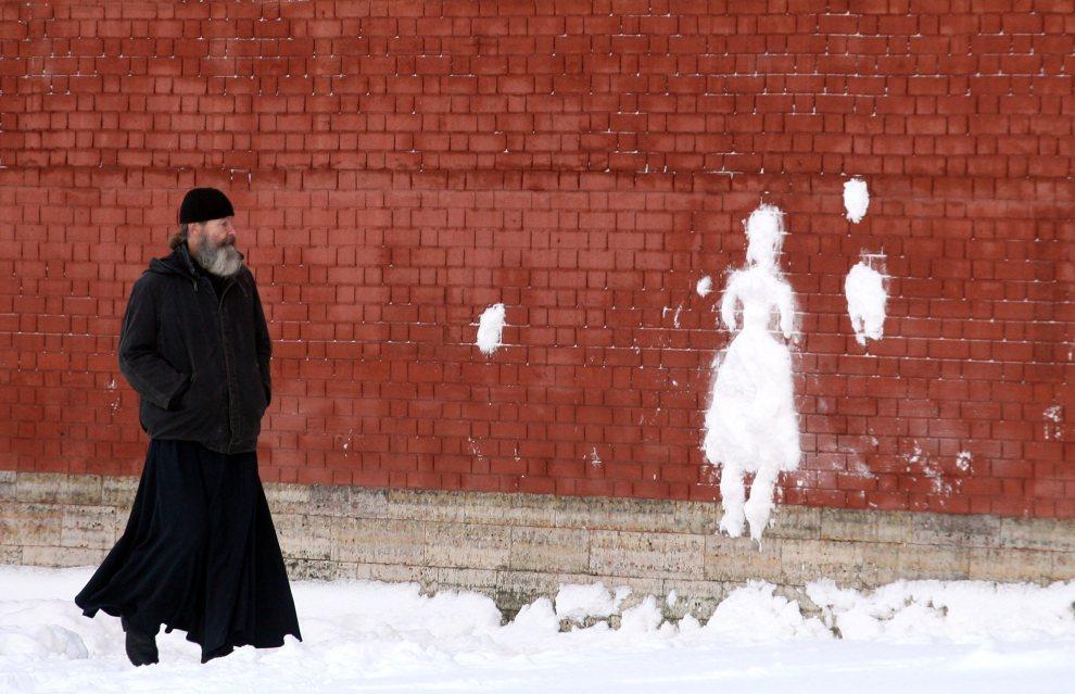 18. ROSJA, Petersburg, 20 stycznia 2011: Pop przechodzi obok śnieżnej sylwetki kobiety odciśniętej na murach Twierdzy Pietropawłowskiej. AFP PHOTO / KIRILL KUDRYAVTSEV