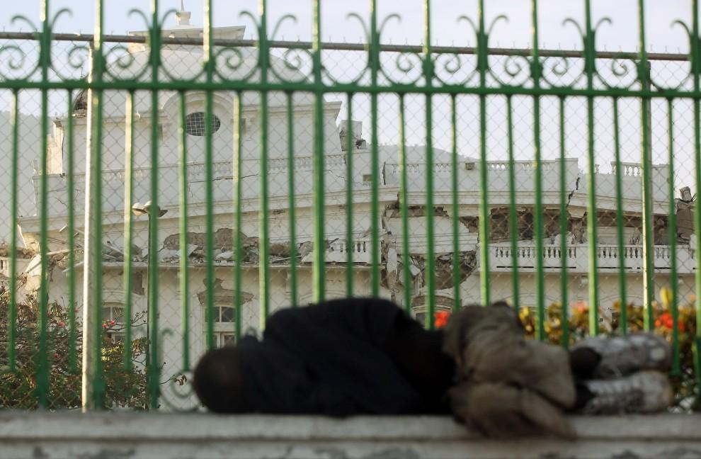 19. HAITI, Port-au-Prince, 12 stycznia 2011: Mężczyzna śpi przed uszkodzonym pałacem prezydenckim. (Foto: Mario Tama/Getty Images)