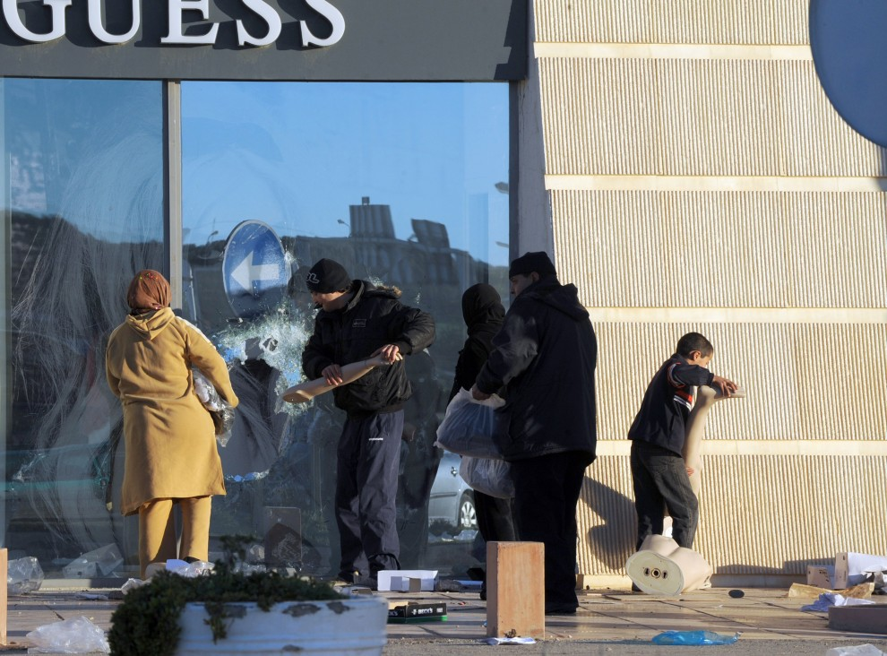 21. TUNEZJA, Tunis, 15 stycznia 2011: Ludzie wybijają szybę w jednym z butików w centrum miasta. AFP PHOTO / FETHI BELAID