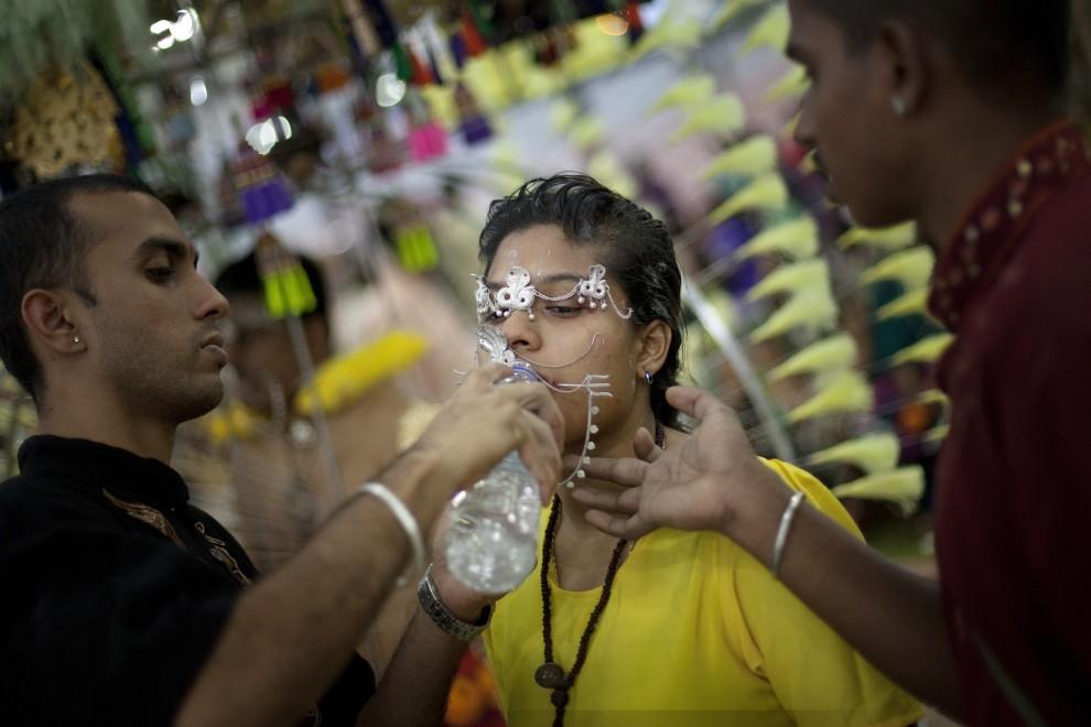 21. SINGAPUR, 20 stycznia 2011: Kobieta z przekłutymi policzkami pije wodę. (Foto: Chris McGrath/Getty Images)
