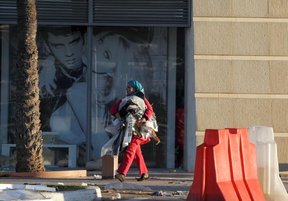 22. TUNEZJA, Tunis, 15 stycznia 2011: Kobieta wynosi ubrania ze splądrowanego sklepu. AFP PHOTO / FETHI BELAID