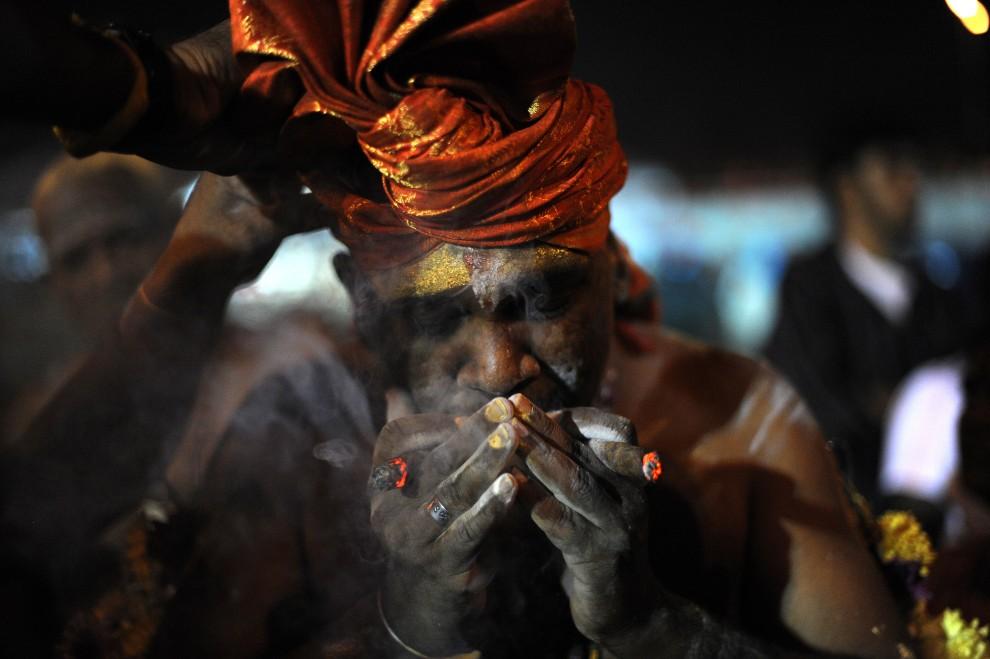 23. MALEZJA, Kuala Lumpur, 30 stycznia 2010: Mężczyzna zaciąga się cygarami w drodze do Jaskini Batu. AFP PHOTO/Saeed KHAN