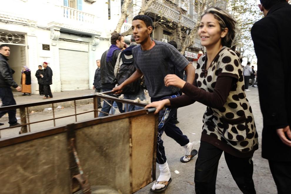 23. TUNEZJA, Tunis, 15 stycznia 2011: Mieszkańcy jednej z dzielnic biegną w kierunku zniszczonego sklepu. AFP PHOTO / FRED DUFOUR