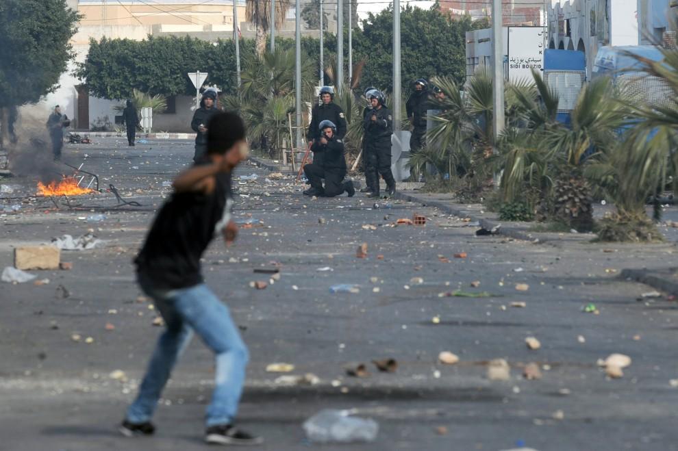 24. TUNEZJA, Regueb, 10 stycznia 2011: Funkcjonariusz służb porządkowy przymierza się do strzału podczas strać na ulicy. AFP PHOTO/STR