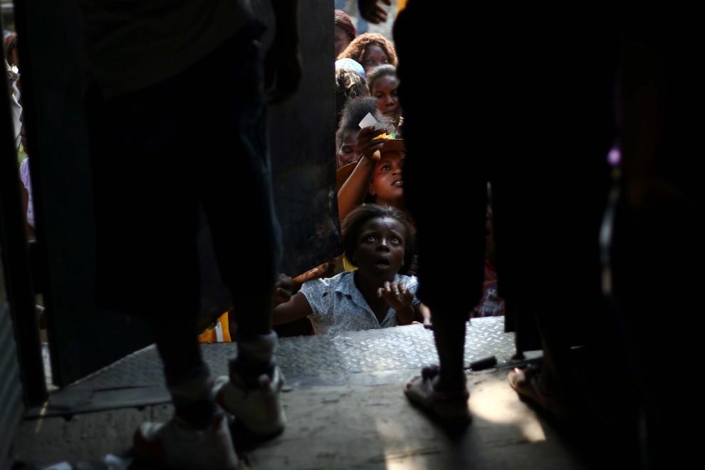 24. HAITI, Port-au-Prince, 8 stycznia 2011: Grupa ludzi czeka na dostawę żywności. Hector Retamal / AFP