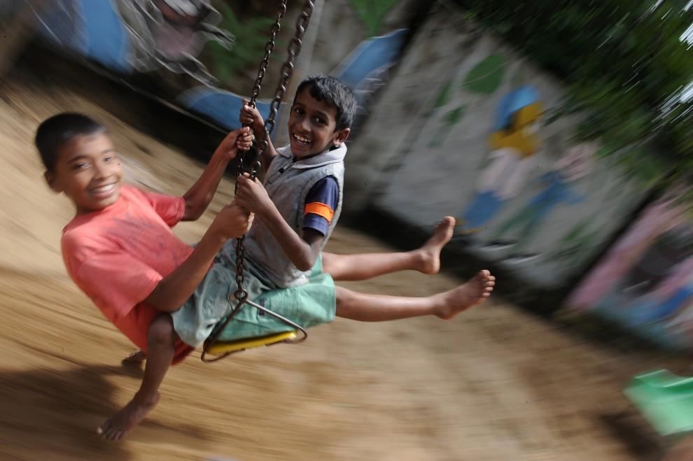 25. SRI LANKA, Batticaloa, 14 stycznia 2011: Chłopcy bawią się w obozie zamieszkiwanym przez ofiary powodzi. AFP PHOTO/Lakruwan WANNIARACHCHI