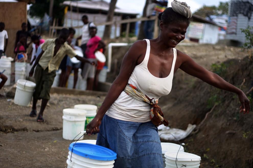 25. HAITI, Port-au-Prince, 9 stycznia 2011: Kobieta niosąca pojemniki z wodą. AFP PHOTO / Hector Retamal