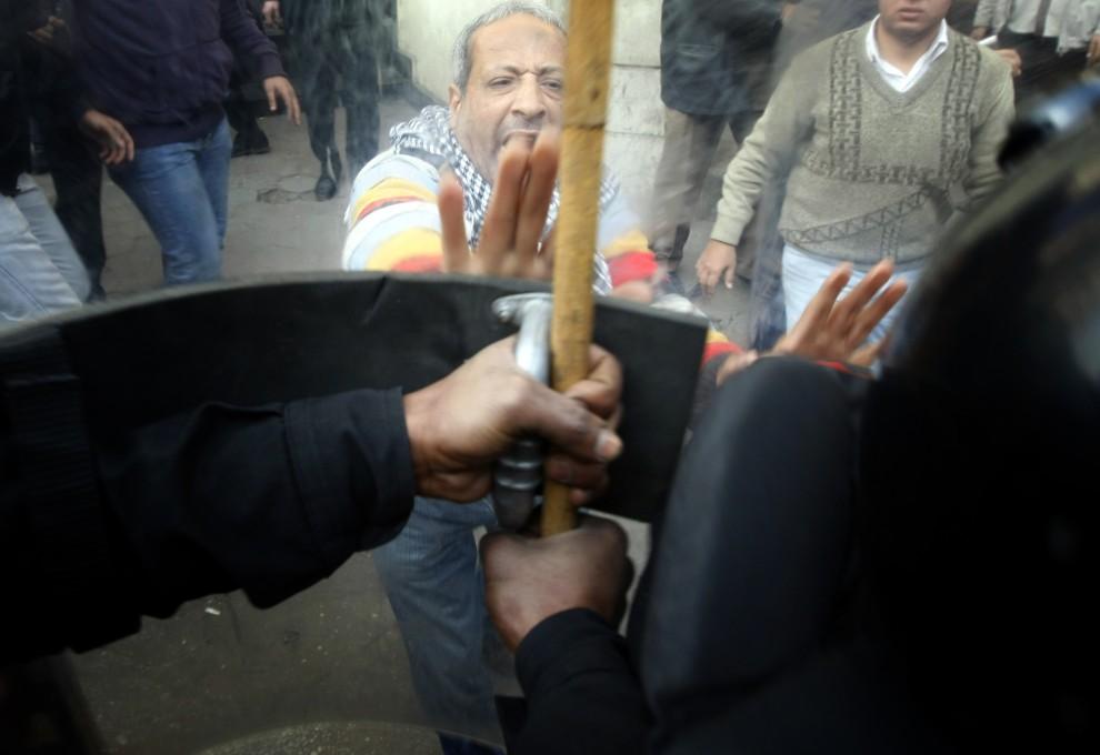 26. EGIPT, Kair, 26 stycznia 2011: Mężczyzna przepycha się z policjantami zasłoniętymi tarczami. AFP PHOTO/MOHAMMED ABED