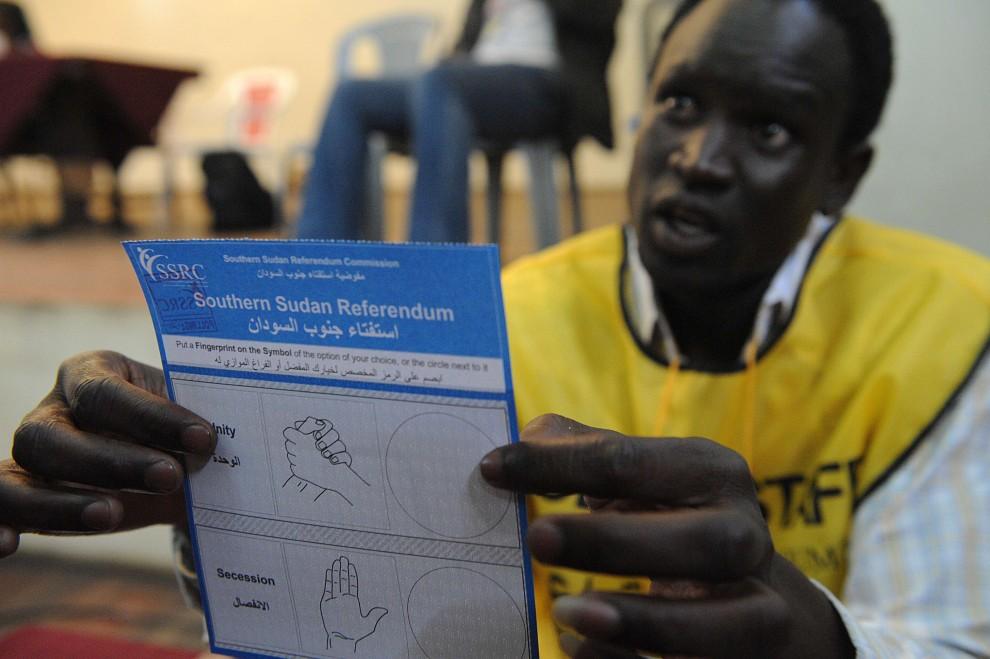 24. KENIA, Nairobi, 9 stycznia 2011: Członek komisji wyborczej pokazuje kartę do głosowania Sudańczykowi mieszkającemu w Kenii. AFP PHOTO / SIMON MAINA