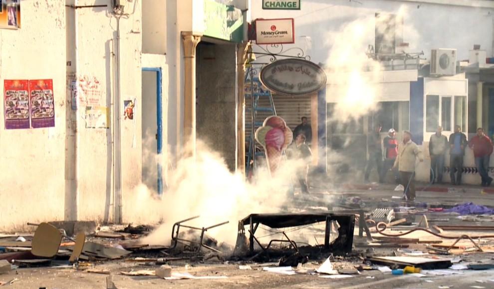 27. TUNEZJA, Hammamet, 13 stycznia 2011: Ludzie stoją przed podpalonym w trakcie zamieszek budynkiem. AFP PHOTO / CLOTILDE GOURLET