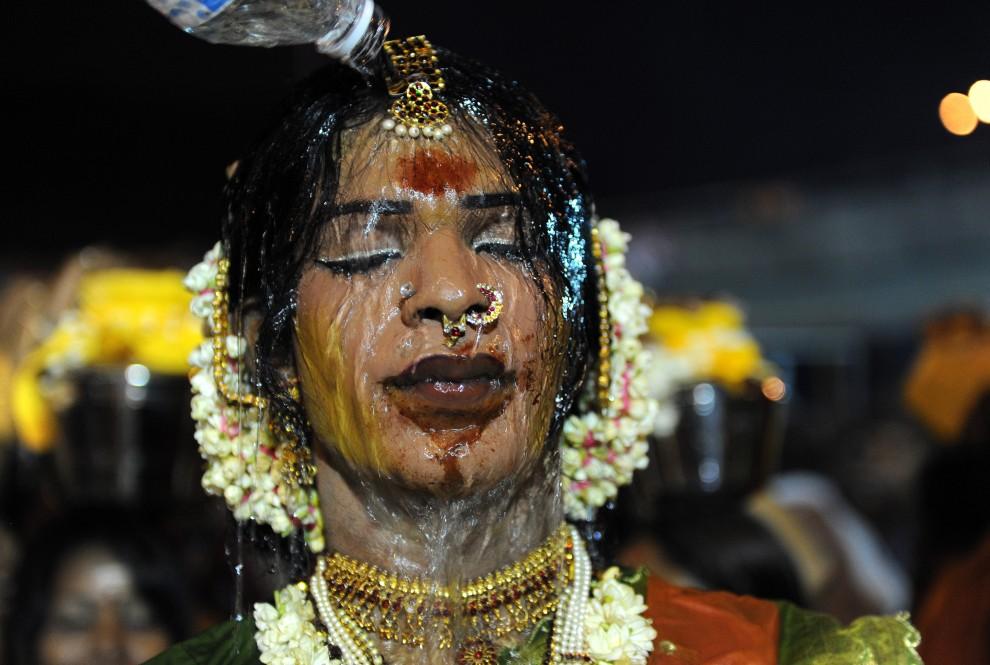 29. MALEZJA, Kuala Lumpur, 30 stycznia 2010: Mężczyzna oblewa wodą twarz uczestnika procesji. AFP PHOTO/Saeed KHAN