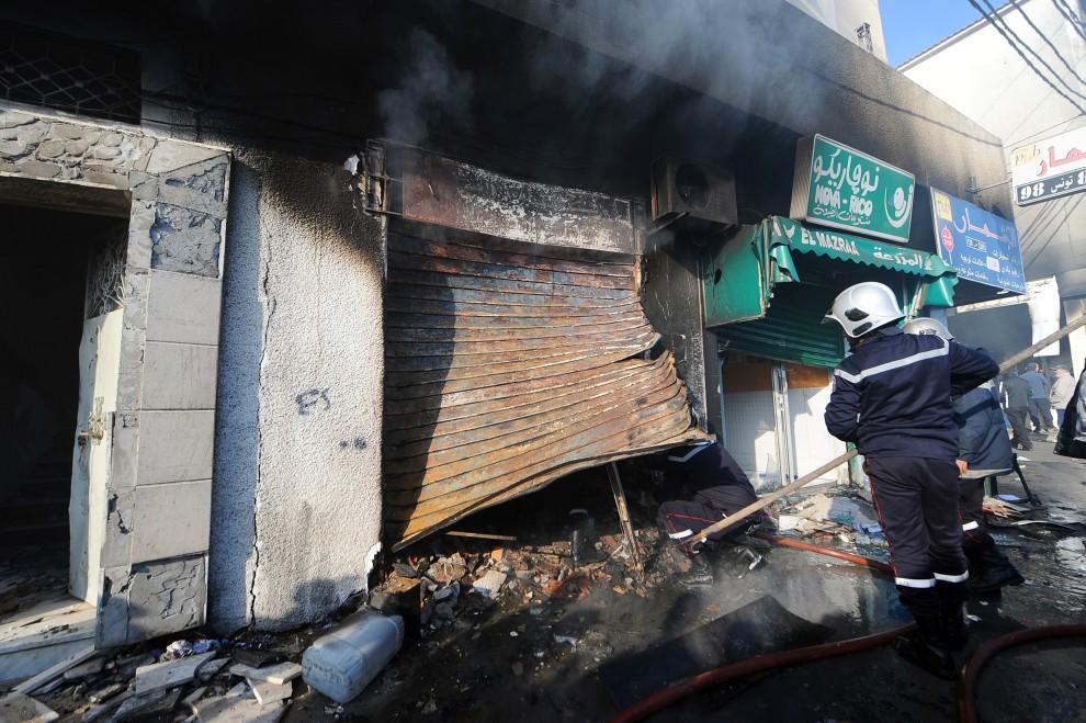 29. TUNEZJA, Tunis, 13 stycznia 2011: Strażacy dogaszają pozostałości jednego ze sklepów w centrum handlowym. AFP PHOTO / FETHI BELAID