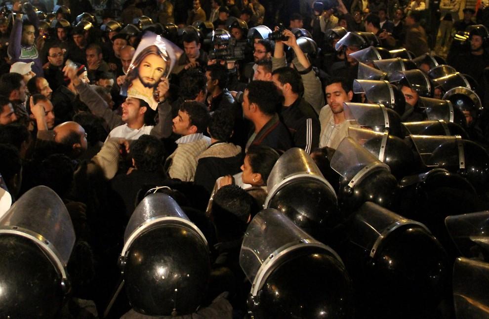 2. EGIPT, Kair, 3 stycznia 2011: Chrześcijanie i muzułmanie, pod nadzorem policji, protestują przeciw zamachowi, do jakiego doszło przed koptyjską świątynią   w Aleksandrii na przełomie roku. Zginęło wówczas 21 osób. AFP PHOTO/STR