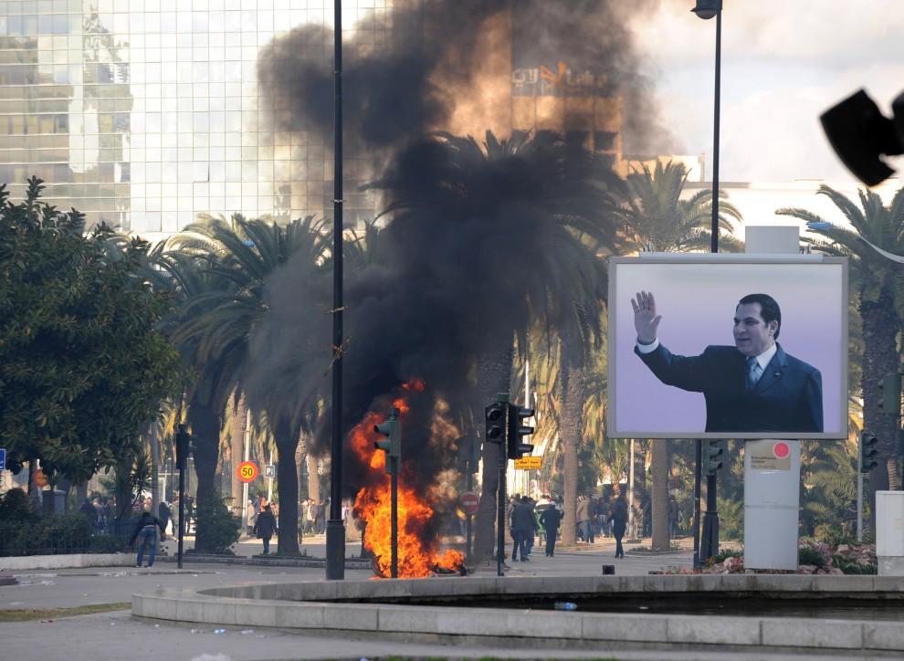 2. TUNEZJA, Tunis, 14 stycznia 2011: Dym z podpalonych śmieci unosi się w pobliżu billboard z wizerunkiem prezydenta  Zine El Abidine Ben Aliego. AFP PHOTO / FETHI BELAID
