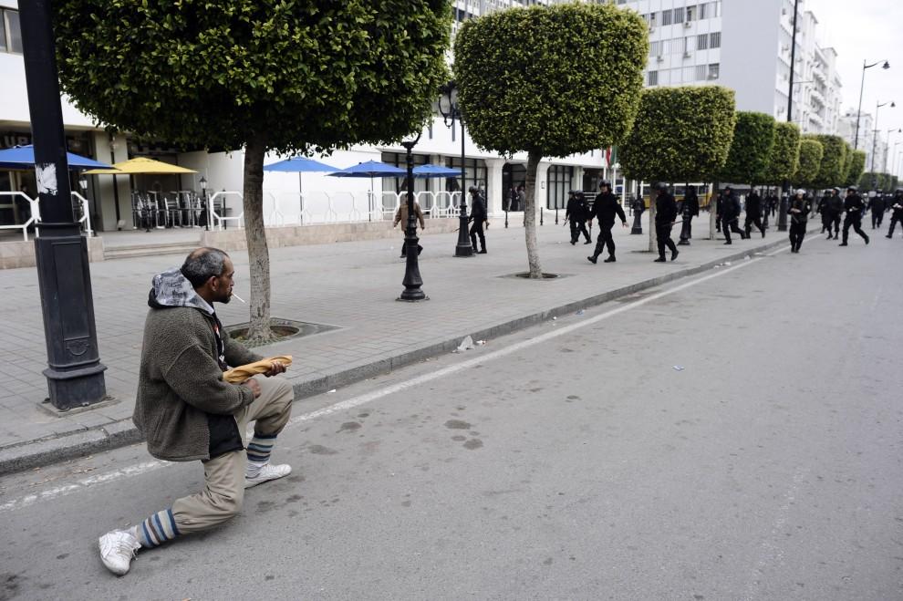 2. TUNEZJA, Tunis, 18 stycznia 2011: Tunezyjczyk podczas demonstracji opozycjonistów gestykuluje w kierunku oddziałów policji. AFP PHOTO / FRED DUFOUR