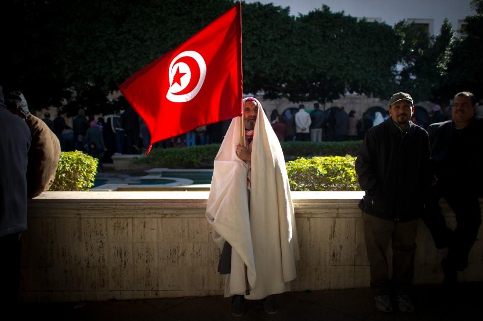 2. TUNEZJA, Tunis, 22 stycznia 2011: Mężczyzna z flagą Tunezji podczas demonstracji w centrum miasta. AFP PHOTO / MARTIN BUREAU