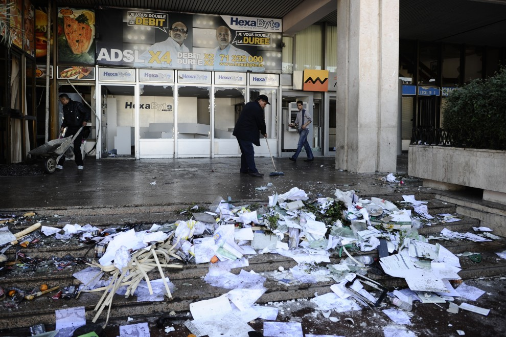 30. TUNEZJA, Tunis, 15 stycznia 2011: Mężczyźni sprzątają wnętrze zdewastowanego dworca kolejowego. AFP PHOTO / FRED DUFOUR