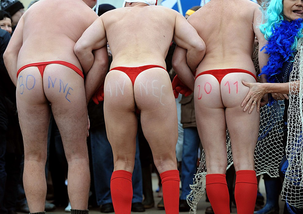 """30. FRANCJA, Dunkierka, 1 stycznia 2011: Napis """"Szczęśliwego Roku 2011"""" na pośladkach mężczyzn uczestniczących w noworocznej kąpieli w Morzu Północnym. AFP PHOTO PHILIPPE HUGUEN"""