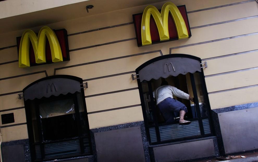 30. EGIPT, Kair, 30 stycznia 2011: Mężczyzna wchodzi przez okno do zniszczonego lokalu McDonald's. (Foto: Chris Hondros/Getty Images)