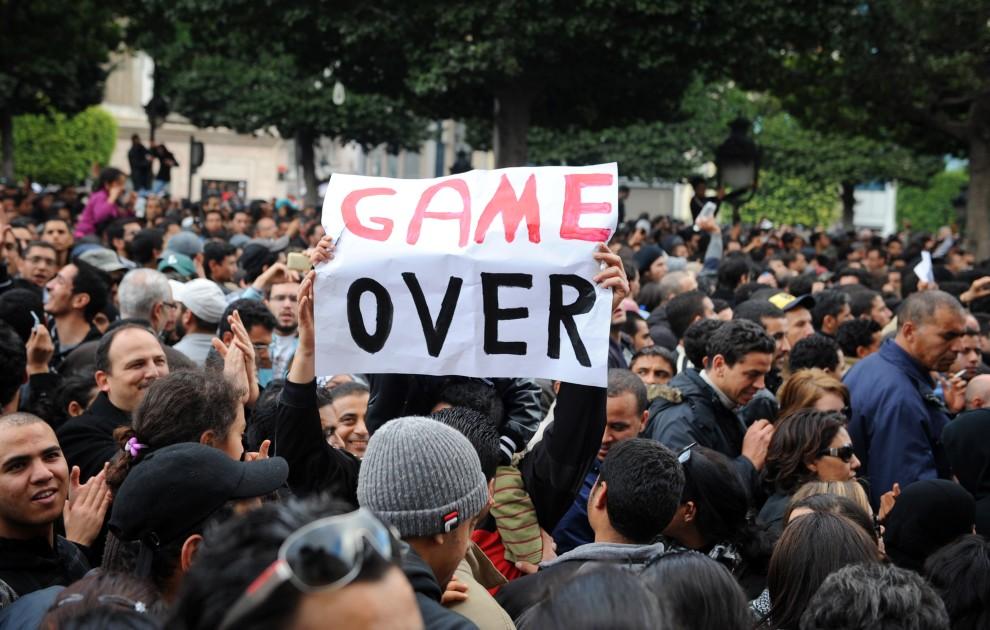"""33. TUNEZJA, Tunis, 14 stycznia 2011: Demonstrujący mężczyzna trzyma plakat z napisem """"Koniec gry"""". AFP PHOTO / FETHI BELAID"""