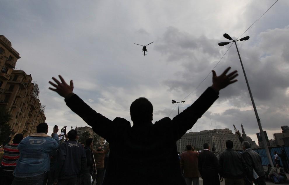 33. EGIPT, Kair, 30 stycznia 2011: Ludzie zebrani na centralnym placu w Kairze gestykulują w kierunku policyjnego śmigłowca. (Foto: Peter Macdiarmid/Getty Images)