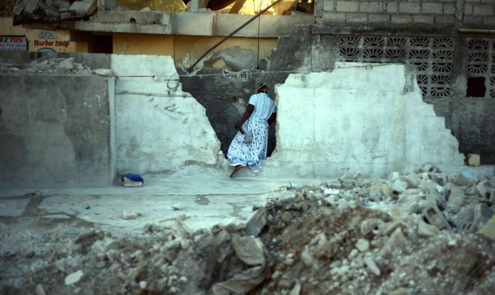 34. HAITI, Port-au-Prince, 5 stycznia 2011: Kobieta przechadza się wśród gruzów zniszczonych budynków. AFP PHOTO / Hector RETAMAL