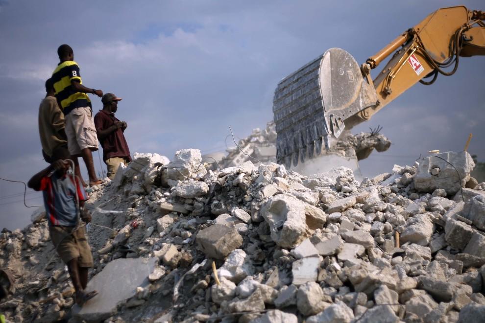 38. HAITI, Port-au-Prince, 8 stycznia 2011: Grupa mężczyzn zbiera złom na gruzowisku. Hector Retamal / AFP