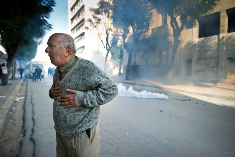 3. TUNEZJA, Tunis, 17 stycznia 2011: Starszy mężczyzna stra się złapać oddech, dławiony gazem wystrzelonym przez policję. AFP PHOTO / MARTIN BUREAU