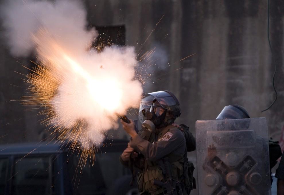 4. IZRAEL, Jerozolima, 19 stycznia 2011: Izraelski policjant strzela w kierunku granicy z Palestyną, skąd rzucane były kamienie. AFP PHOTO/AHMAD GHARABLI