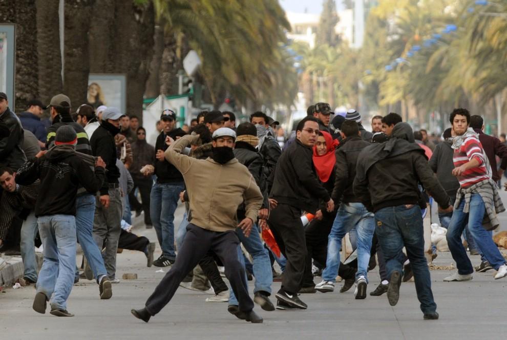4. TUNEZJA, Tunis, 14 stycznia 2011: Demonstrujący Tunezyjczycy obrzucają policjantów kamieniami. AFP PHOTO / FETHI BELAID