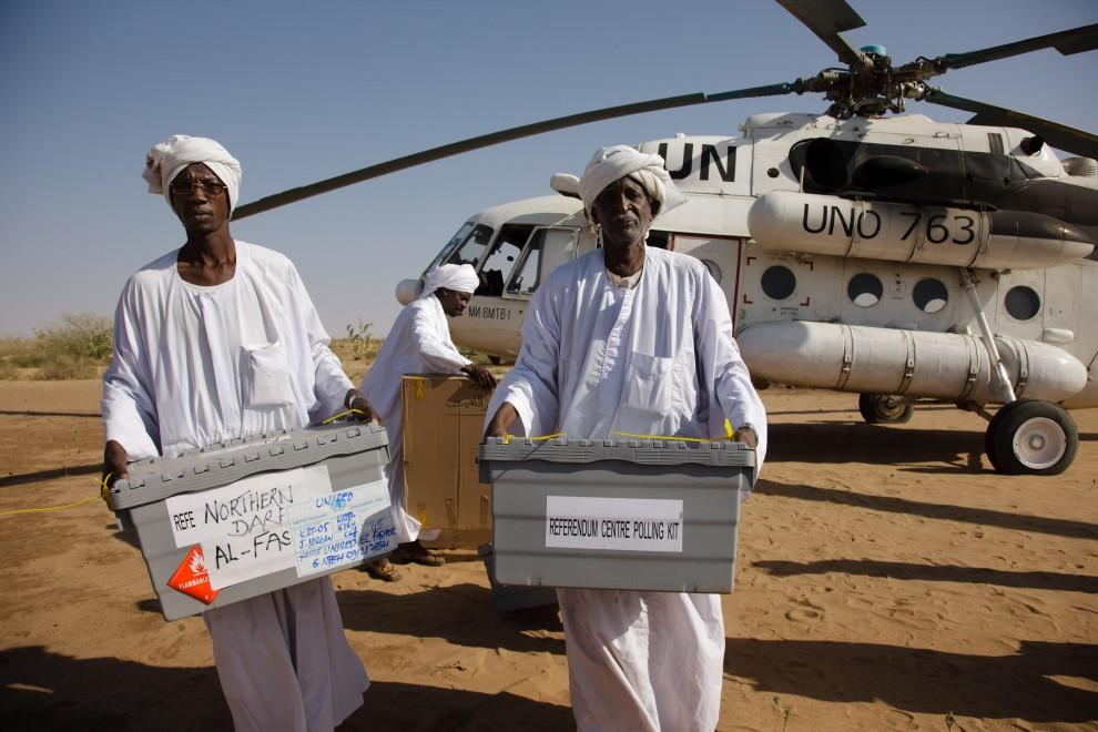 4. SUDAN, Darfur, 6 stycznia 2011: Sudańczycy niosą urny do głosowania przywiezione na pokładzie  śmigłowca ONZ. AFP PHOTO/HO/UNAMID/OLIVIER CHASSOT