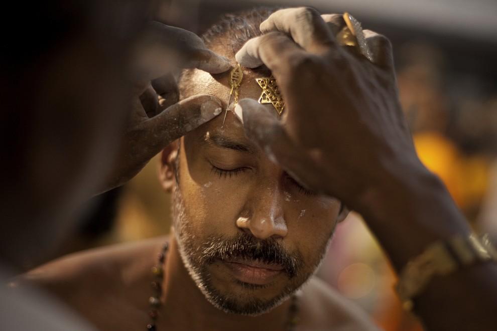 5. SINGAPUR, 20 stycznia 2011: Mężczyzna nakłuwa czoło uczestnika procesji. (Foto: Chris McGrath/Getty Images)