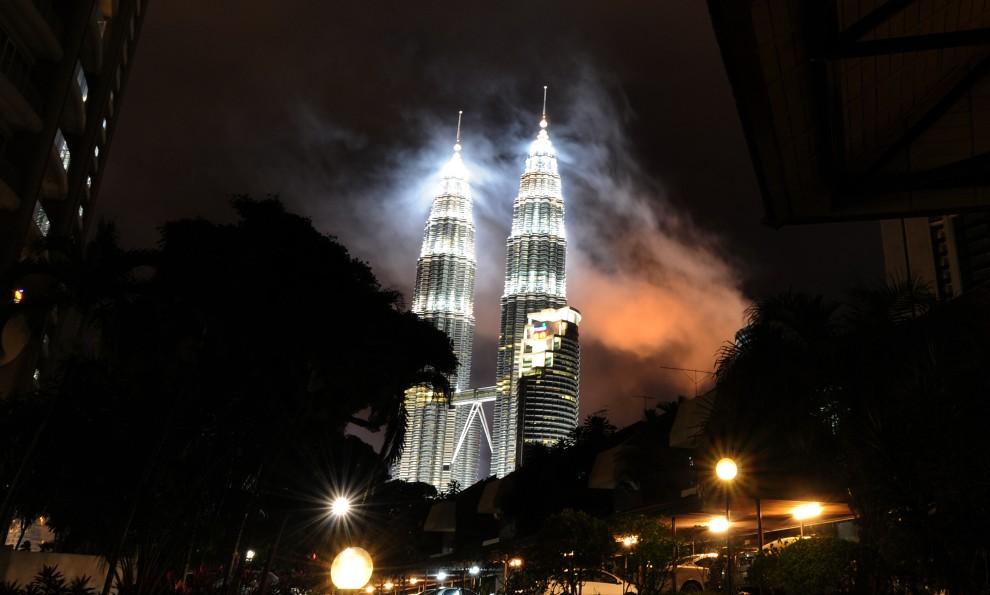 6. MELEZJA, Kuala Lumpur, 1 stycznia 2011: Dym z odpalanych sztucznych ogni unosi się nad wieże  Petronas Twin Towers. AFP PHOTO / Saeed Khan
